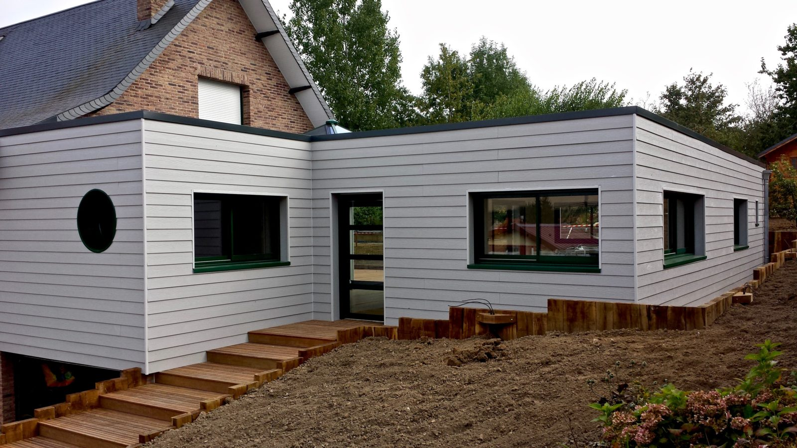 Extension en composite sureleveesur maison traditionnelle
